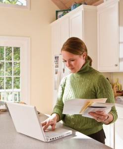 Woman on Comp in Kitchen with Bills